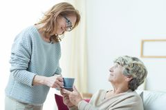 Care assistant helping elderly lady. Smiling senior care assistant helping elderly lady stock photo