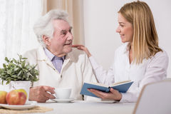 Care assistant reading book. Care assistant and elder men reading book Stock Images