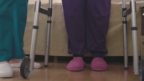 Care assistant teaching elder disabled woman how to walk with walker stock video footage