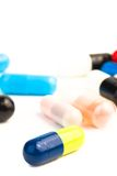 Care with colored pills. Close up of one colorful pill in front of unfocused pills on white background Royalty Free Stock Photos