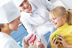Care dental hygiene. Image of dentist showing care dental hygiene to little girl with assistant near by Stock Photo