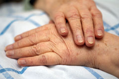 Care-dependent person. Old wrinkled hands of a care-dependent person lying in bed Stock Image