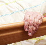 Care-dependent person. Hand of a care-dependent person in bed Stock Photography