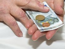 Care-dependent person holding money. Hands of an old care-dependent holding euro Stock Photo