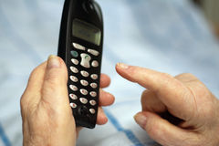 Care-dependent person making phone call. Old wrinkled hands of a care-dependent person making a phone call Stock Photography
