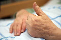 Care-dependent person showing thumbs up. Old wrinkled hands of a care-dependent person showing thumbs up Stock Photos