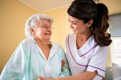 Care of the elderly at nursing home. Nurse helps to senior women to walk Royalty Free Stock Images