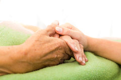 Care for Elderly. Social services nurse holding elderly woman's hand with care stock photo