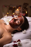 Care for face and body spa. Girl with a chocolate mask on his face in a soothing atmosphere with candles Royalty Free Stock Images