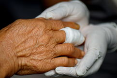 Care giver by doctor. Fingers wound elderly care on nurse hand Royalty Free Stock Photos
