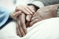 Care. Hand of women touching senior men in clinic royalty free stock image