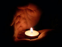 Care hands. Two palms take care of candle fire Stock Images