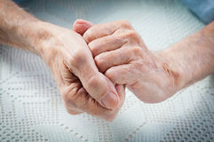 Care is at home of elderly. Old people holding hands. Closeup royalty free stock image