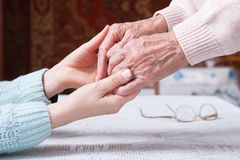 Care is at home of elderly. Senior woman with their caregiver at home. Concept of health care for elderly old people. Disabled. Elderly woman holding hands Stock Photos