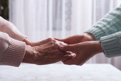 Care is at home of elderly. Senior woman with their caregiver at home. Concept of health care for elderly old people. Disabled. Elderly woman holding hands Royalty Free Stock Image