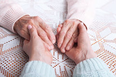 Care is at home of elderly. Senior woman with their caregiver at home. Concept of health care for elderly old people. Disabled. Elderly woman holding hands Stock Image