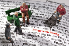 Care insurance in old age. Topic Care insurance: Model figures of old people on an encyclopedia on which the German word Pflegeversicherung is to be read royalty free stock photography