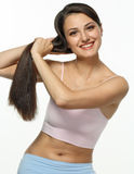 Daily care of long hair. The girl combs beautiful chestnut hair and smiles in the morning Stock Photo