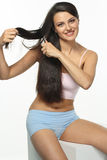Daily care of long hair. The girl combs beautiful chestnut hair and smiles in the morning Stock Photography
