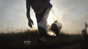 Care about nature. Volunteer girl collects trash in the trash bag. Trash-free planet concept. Nature cleaning, volunteer stock video footage