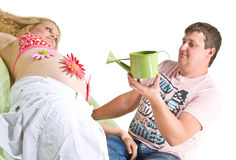 Care in pregnancy. A metaphorical image showing a man watering artificial flowers on his pregnant wife's stomach Stock Photo