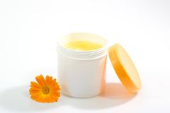 Care product. Cream pot with marigold on white background Stock Photo