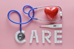 CARE word made from medicine pills and stethoscope, temperature, red heart on pink background. Concept of Valentine`s Day royalty free stock image