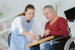 Care worker giving older man dinner stock photos