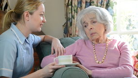 Care Worker Talking To Depressed Senior Woman At Home stock footage