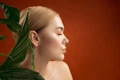 Cared lady giving preference to naturalness. Profile of tranquil girl with perfect skin near green leaves. Her eyes are closed. Copy space in right side Royalty Free Stock Image