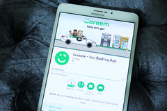 Careem car booking app. Downloading careem car booking app from google play store on samsung tablet. careem is car booking app for a safe, reliable and royalty free stock images