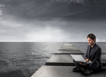 Career. Businessman sitting on a pad over the ocean and using a laptop Stock Photo