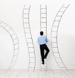 Career choices concept. Career choices and opportunities concept - businessman climbing the right ladder Royalty Free Stock Photo