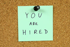 Career concept. Green small sticky note on an office cork bulletin board. You are hired message. Career success, new employment Royalty Free Stock Photo