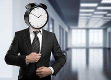 Career concept. Abstract alarm clock headed businessman standing on blurry office interior background with copy space. Career concept Royalty Free Stock Image