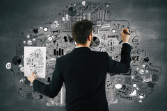 Career concept. Back view of young businessman copying text from paper to wall. Career concept Royalty Free Stock Image