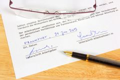 Career concept. Business objects - full time fictitious employment contract in German language ready to sign with ink pen. Germany career Royalty Free Stock Image