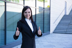 Career concept - business woman thumbs up over modern city backg Stock Image
