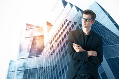 Career concept. Thoughtful young businessman with smartphone standing on bright city background. Career concept Royalty Free Stock Image