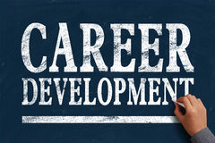 Career development. Businessman is writing Career development text on blue chalkboard Royalty Free Stock Images