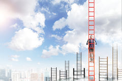 Career growth. A young businessman in a suit climbing a red ladder, many other ladders behind, city view and blue sky at the background. Concept of career Stock Images