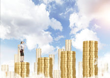 Career growth. A young businesswoman looking in front ready to climb a career ladder in shape of a bar chart made of coins, blue sky at the background. Concept Stock Image
