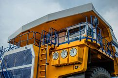 Career heavy dump truck Belaz. Yellow cab of a large car. Close-up royalty free stock image