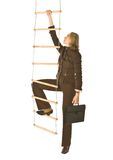 Career ladder. An isolated photo of a businesswoman climbing a rope-ladder Royalty Free Stock Photography