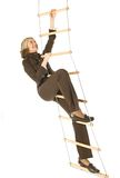 Career ladder. An isolated photo of a businesswoman climbing a rope-ladder Stock Image