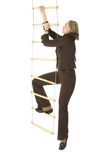 Career ladder. An isolated photo of a businesswoman climbing a rope-ladder Royalty Free Stock Images