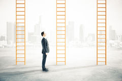 Career ladders city background. Businessman looking at career ladders on blurry city background royalty free stock photography