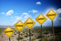 Career level concept with different stages of professional experience on yellow road signs on desert landscape stock photos