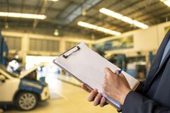 This career man saleman business inspection writing note on note. Pad or book, paper with car service blurred background.for transport automobile automotive Royalty Free Stock Photo