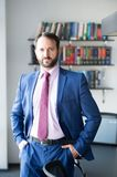 Career, profession, work. Businessman or director pose at workplace. Business, entrepreneurship concept. Fashion, style, dress code. Man with beard in blue Stock Photos